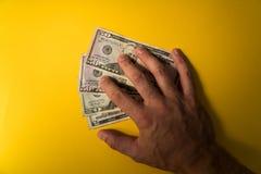 La main du ` s d'homme a couvert les billets de banque des dollars Protection de votre argent Manque d'argent Dollars de plan rap Photographie stock