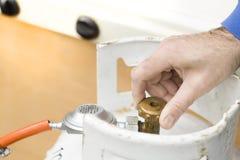 La main du ` s d'homme dévisse la valve de la bouteille de gaz Photos stock