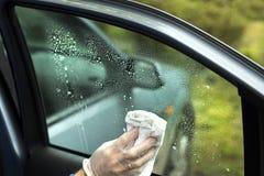 La main du ` s d'homme essuie le verre du ` s de voiture avec un tissu Images stock