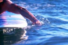 La main du ` s d'homme flottant sur le paddleboard image stock