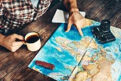 La main du ` s d'homme indique un itinéraire sur une carte de papier Une autre main tient une tasse de thé L'homme est inspiré pa photo stock