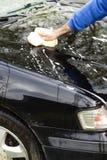 La main du ` s d'homme lave le masque d'éponge du ` s de voiture avec l'abondance de la mousse Photographie stock