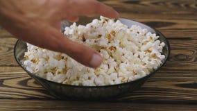 La main du ` s d'homme prend le maïs éclaté d'une glace banque de vidéos