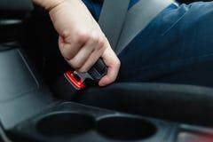 La main du ` s d'hommes attache la ceinture de sécurité de la voiture Photos libres de droits