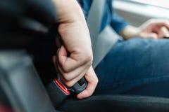 La main du ` s d'hommes attache la ceinture de sécurité de la voiture Images libres de droits