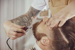 La main du ` s de coiffeur tient la tondeuse tout en coupant la barbe Image stock