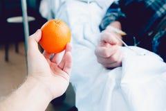 La main du ` s de docteur tient l'orange contre le compte-gouttes photo libre de droits