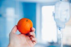 La main du ` s de docteur tient l'orange contre le compte-gouttes images stock