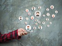 La main du ` s de femme avec des cercles de téléphone et intègrent des personnes communiquent Images stock