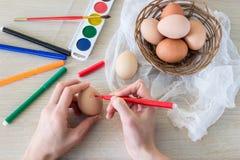 La main du ` s de femme peint le marqueur de nourriture d'oeufs du ` s de poule pour Pâques Photographie stock libre de droits