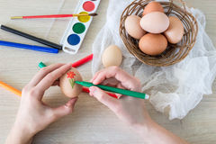 La main du ` s de femme peint le marqueur de nourriture d'oeufs du ` s de poule pour Pâques Photos stock
