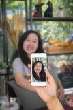 La main du ` s de femme utilisant le téléphone intelligent prennent à une photo un sourire asiatique de femmes heureusement Photos stock