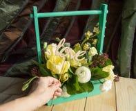 La main du ` s de femmes tenant le haut de forme en bois avec amour de mot, boîte avec le ressort fleurit Image libre de droits