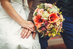 La main du ` s de jeune mariée se trouve sur la main du ` s de jeune marié avec un bouquet de mariage d'anneau du ` s de jeune ma Photo libre de droits