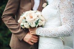 La main du ` s de jeune mariée se trouve sur la main du ` s de jeune marié avec un bouquet de mariage d'anneau du ` s de jeune ma Images stock