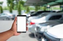 la main du téléphone portable de prise de l'homme au-dessus du stationnement brouillé de voiture avec Photographie stock