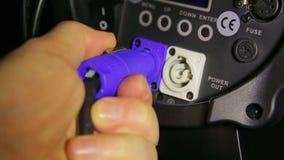 La main du travailleur de bloc d'éclairage relie le fil électrique de canalisations au projecteur de profil banque de vidéos
