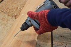 La main du travailleur fore un trou avec la planche en bois utilisant la machine de foret électrique dans l'atelier Photos stock
