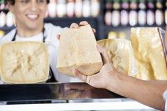 La main du vendeur passant le fromage au collègue dans la boutique Photographie stock libre de droits