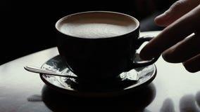 La main en gros plan d'homme prend une tasse de café avec du lait d'une table en bois dans un café clips vidéos