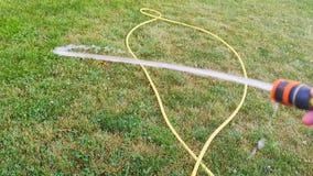 La main en gros plan et masculine tient un tuyau de arrosage Herbe de arrosage sur la pelouse banque de vidéos