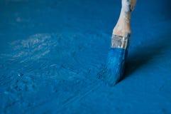 la main en jaune de gant a peint le bleu avec l'os, fin  photo stock