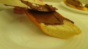 La main enduit la cuisine de noisette de nutella faisant cuire le closeupchocolate sur le pain préparant la nutrition clips vidéos