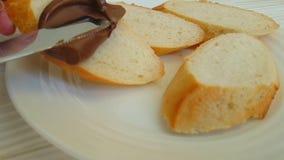 La main enduit la cuisine de noisette de nutella faisant cuire le fond sur le pain préparant la gastronomie de nutrition banque de vidéos