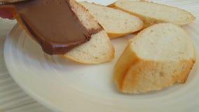 La main enduit le chocolat de cuisine de noisette de nutella sur le pain préparant la nutrition banque de vidéos
