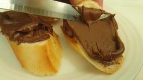 La main enduit le chocolat de cuisine de nutella sur le pain préparant la nutrition banque de vidéos