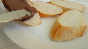 La main enduit le chocolat sur le pain préparant la nutrition banque de vidéos