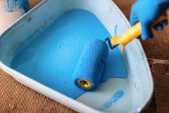 La main enfilée de gants abaisse le rouleau dans le plateau avec la peinture bleue Peintre de services R?paration et d?coration d images libres de droits