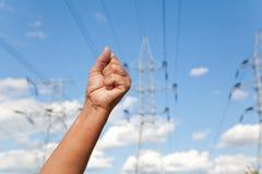La main est serrée dans un poing et des lignes de transport d'énergie agains Photo stock