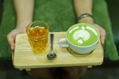 La main et le café et les jeunes chauds de thé vert aiment boire chaud images libres de droits