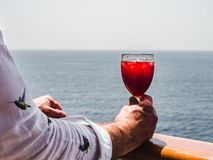 La main et le verre de l'homme avec un cocktail photo stock