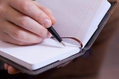 La main femelle écrit des notes dans le cahier Photo libre de droits