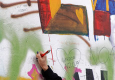 La main femelle écrit sur le mur coloré de graffiti Photos stock