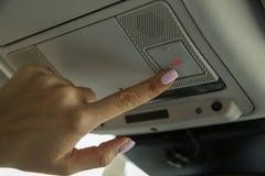 La main femelle appuie sur le bouton de SOS sur le panneau de voiture photographie stock