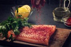 La main femelle arrose un morceau de filet saumon? se trouvant sur une planche ? d?couper en bois avec des ?pices - photo, image image stock
