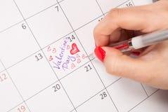 La main femelle avec des coeurs de dessin au crayon forment et des mots dans le calendrier pour le jour de valentines Images stock