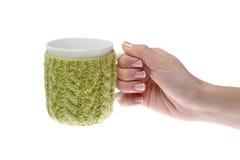 La main femelle avec la manucure tenant une tasse, vert attaché filète Images stock