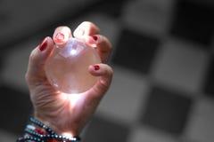 La main femelle avec les clous rouges tient la boule de cristal rose pour l'astrologie photos libres de droits