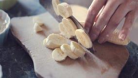 La main femelle coupe sur la banane de morceaux sur le conseil en bois clips vidéos