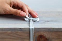 La main femelle délie le ruban sur la boîte en bois de cadeau Images stock