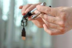 La main femelle détache une partie de la cigarette électronique Images stock