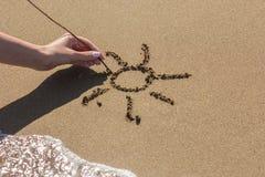 La main femelle dessine le soleil sur le sable près de la mer Image libre de droits
