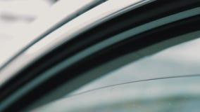 La main femelle donne la carte de mémoire d'écart-type dans la fenêtre de voiture ouverte de cuvette de l'homme banque de vidéos