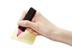 La main femelle est prête pour dessiner avec le marqueur rose et la feuille jaune sur une surface Photographie stock libre de droits
