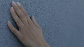La main femelle frotte doucement le mur de texture banque de vidéos