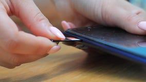 La main femelle insère une carte de sim dans le téléphone banque de vidéos